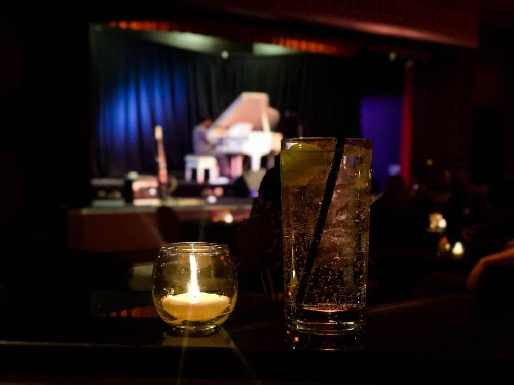 Man performing at piano and cocktail on table